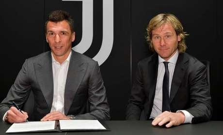 Mandzukic assinou contrato ao lado de Nedved, ídolo e agora diretor da Juventus (Divulgação)