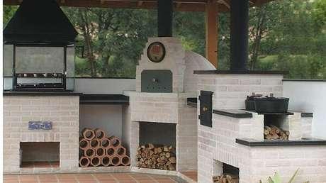 7 – Área de lazer pequena com churrasqueira e fogão a lenha com tijolinho claro. Fonte: Dcore Você