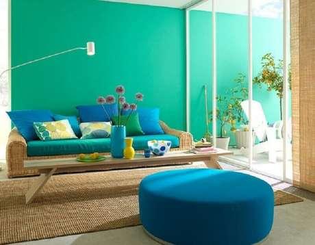 21. Decoração com parede verde água para sala com sofá de vime e puff redondo azul – Foto: Jaeger Arquitetura