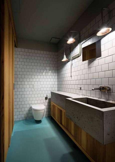 26. Aqui a decoração do banheiro contou com a cor verde água no piso e uma bancada de cimento trazendo um toque industrial para a decoração – Foto: Mauricio Gebara Arquitetura