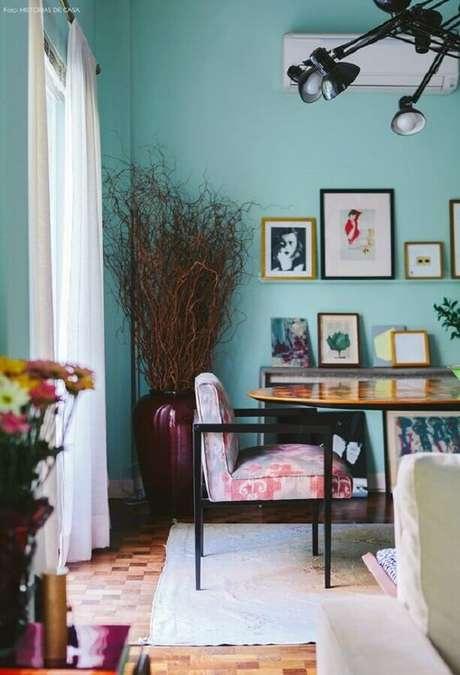 39. Parede verde água para decoração da sala de jantar com quadrinhos na parede e luminária de teto moderna – Foto: Pinterest