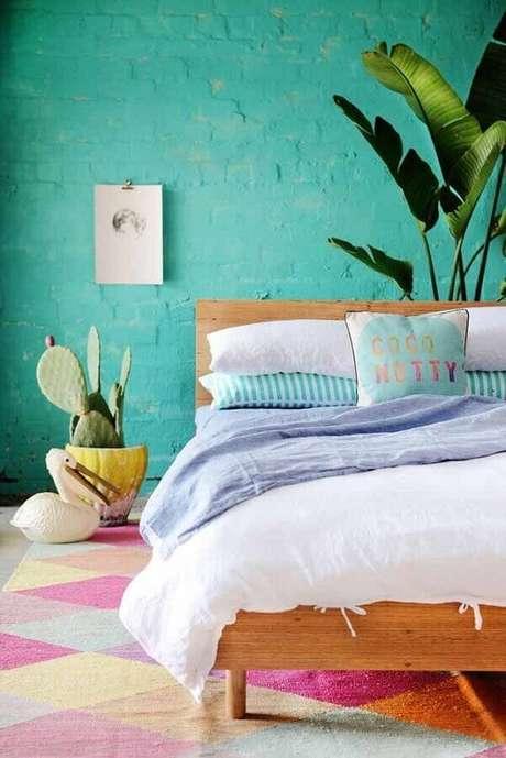 54. Decoração com estilo leve para quarto com tapete colorido, parede verde água e vasos de plantas – Foto: Archzine