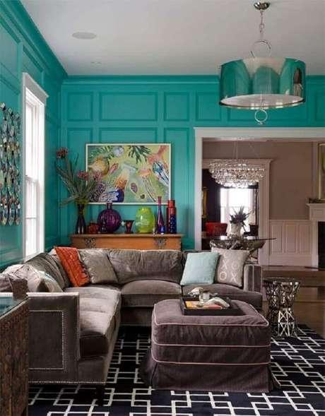57. Parede verde água com boiserie para decoração de sla com sofá de canto e vasos coloridos – Foto: Air Freshener