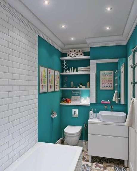 58. Banheiro verde água decorado com parede de tijolinho e quadrinhos decorativos – Foto: FrenchIdees