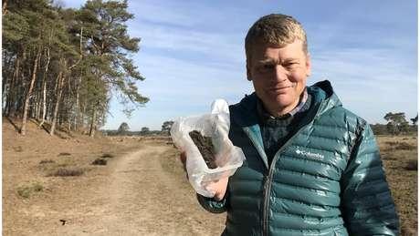 Apresentador da BBC Tom Heap mostra caixa com fezes de lobos na Holanda