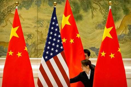 Funcionários organizam bandeiras dos Estados Unidos e China antes de rodada de negociações em Pequim 14/02/2019 Mark Schiefelbein/Pool via REUTERS