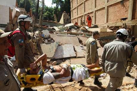 Bombeiros carregam vítima retirada dos escombros de dois prédios que desabaram na comunidade da Muzema, na zona oeste do Rio de Janeiro, na manhã desta sexta-feira, 12 de abril de 2019