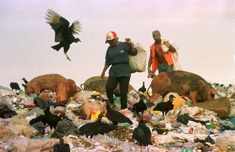 Porcos, urubus e catadores de lixo são vistos no Lixão de Itaoca, em 1999