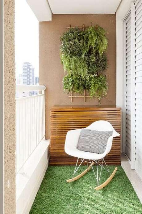 7. Decoração com pequeno jardim vertical e cadeira de balanço para varanda pequena – Foto: Pinosy