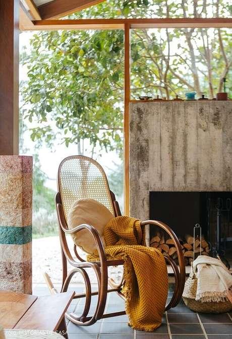 37. Decoração rústica com cadeira de balanço de madeira e lareira – Foto: Histórias de Casa
