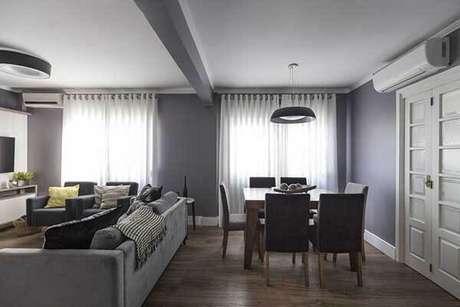 40- Na decoração da sala, os modelos de cortinas com ilhoses foram pendurados em varões. Fonte: MODI Arquitetura e Interiores