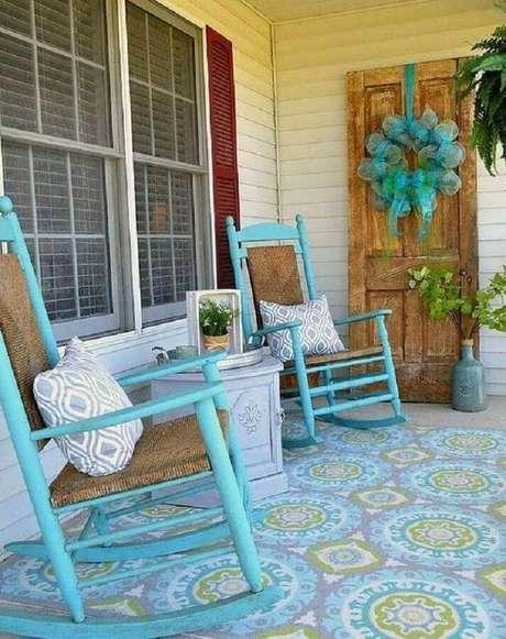 6. Decoração simples com cadeira de balanço para varanda pintada de azul e com piso estampado – Foto: QuitDecor