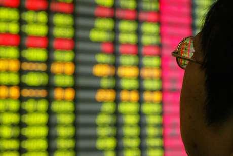 Investidor observa tela com movimento de mercados em Xangai  25/07/2003 REUTERS/Claro Cortes IV