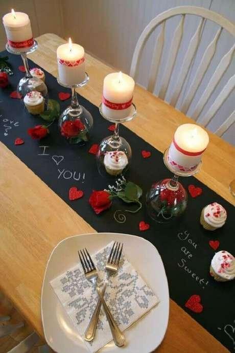 15- A decoração dia das mães foi elaborada com cartolina preta no centro da mesa escrita com frases em giz, flores vermelhas e taças de ponta cabeça utilizadas como castiçais. Fonte: Como Fazer em Casa