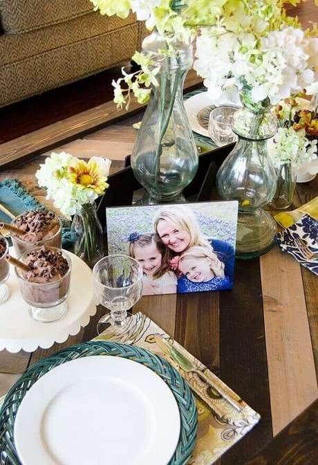 17- A decoração dia das mães tem sobre a mesa arranjos de flores e fotografia da família. Fonte: A Minha Festinha