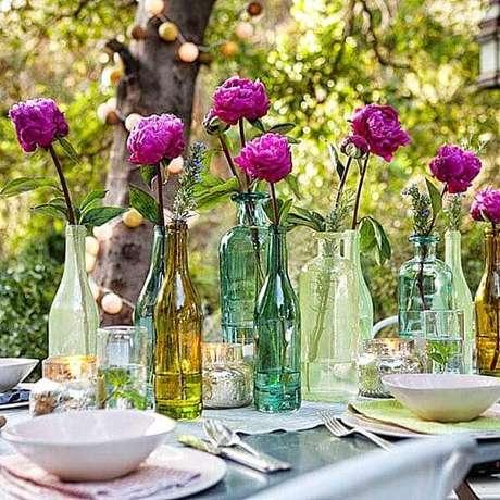 18- A decoração dia das mães em ambiente aberto tem garrafas coloridas em diferentes formatos com flores no centro da mesa. Fonte: Casa para Viver
