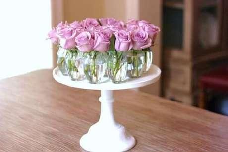 24- Na decoração dia das mães, o arranjo central da mesa é formado por vários vasinhos transparentes com rosas lilás. Fonte: Ambientes de Charme