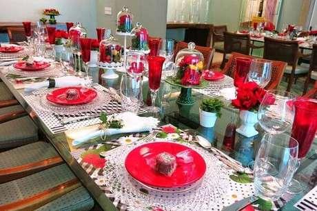 38- A decoração dia das mães em salão tem louças, taças vermelhas e sousplat de crochê. Fonte: Jornal Evolução
