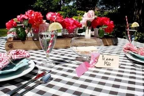 41- A decoração dia das mães em área descoberta tem toalha de mesa xadrez e bandeja rústica com flores. Fonte: ConstruindoDecor