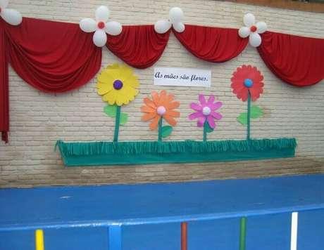 50- A decoração dia das mães na escola tem canteiro com flores de papel e cortina em TNT colados na parede. Fonte: Como Fazer em Casa