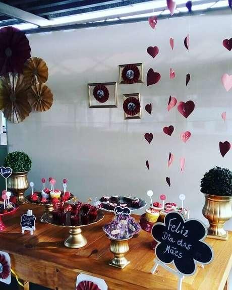 61- A mesa de doces tem pratos dourados combinando com os vasos laterais. Fonte: Eliza Brito Designer eventos