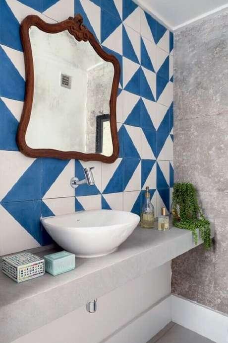 22. Lavabo simples decorado com azulejo azul e branco e espelho com moldura de madeira – Foto: Casa e Festa