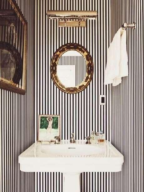 29. Decoração com espelho redondo com moldura dourada para lavabo com papel de parede listrado – Foto: Flat 15