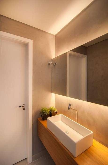 30. Espelho para lavabo decorado em tons neutros com bancada de madeira – Foto: Diseno Interior