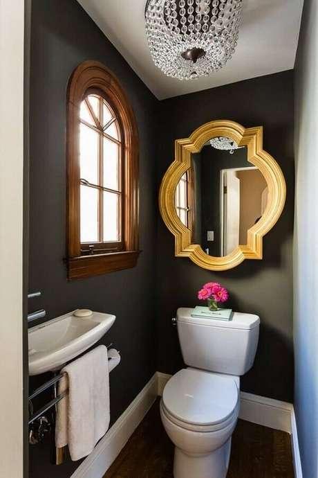 37. Lavabo pequeno decorado com parede pretas e espelho com moldura dourada – Foto: Pinterest