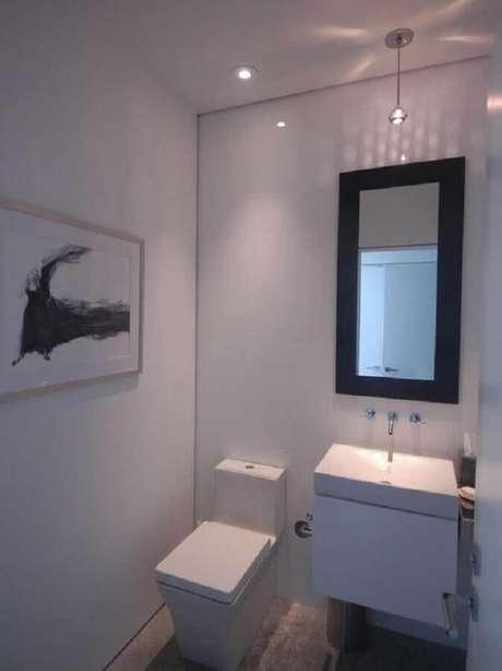 38. Lavabo todo branco decorado com espelho simples de moldura preta – Foto: Mi Limonada