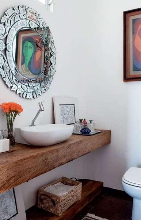 40. Decoração simples com modelo diferente de espelho para lavabo com bancada de madeira – Foto: Casinha Colorida