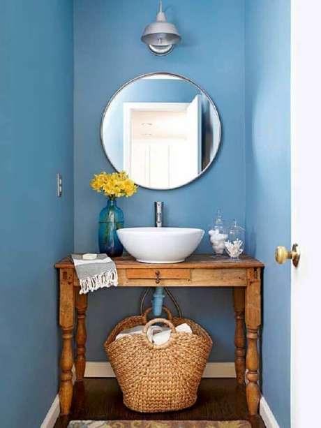 47. Decoração simples com espelho redondo para lavabo com móvel de madeira e parede azul – Foto: Julie Holloway Studio