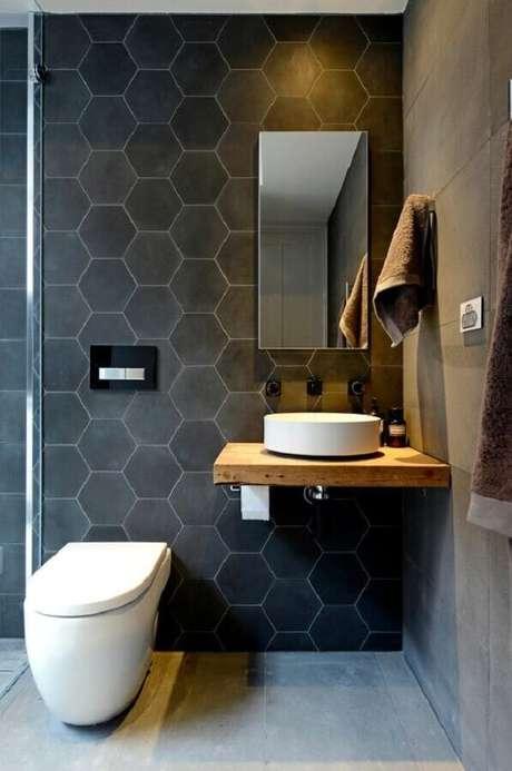 62. Modelo de espelho para lavabo decorado em tons de cinza com pequena bancada de madeira – Foto: Pinterest