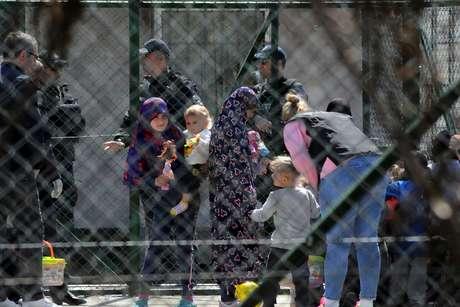 Policiais escoltam mulheres e crianças que são parentes de combatentes do país que lutaram na Síria. 20/4/2019. REUTERS/Laura Hasani -
