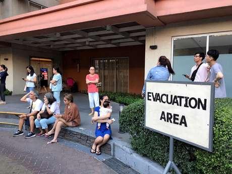 Moradores aguardam do lado de fora de prédio evacuado devido ao terremoto