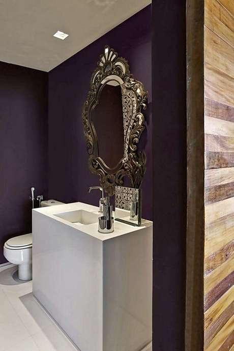 33. Decoração moderna para banheiro com espelho provençal e parede roxa – Foto: Foto Architizer