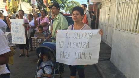 Venezuelanos protestam por conta da pobreza no país com cartazes dizendo que o salário não lhes permite comer e que não há luz, água e/ou gás