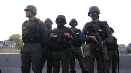 Integrantes de forças militares usando braçadeira azul, em apoio a Guaidó