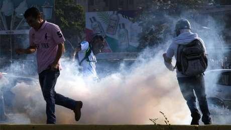 Venezuelanos fogem das bombas de gás lacrimogêneo lançadas pelas forças de segurança em Caracas