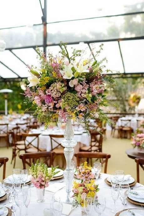 18. Festa de casamento ao ar livre decorada com grande arranjo de flores – Foto: Pinosy