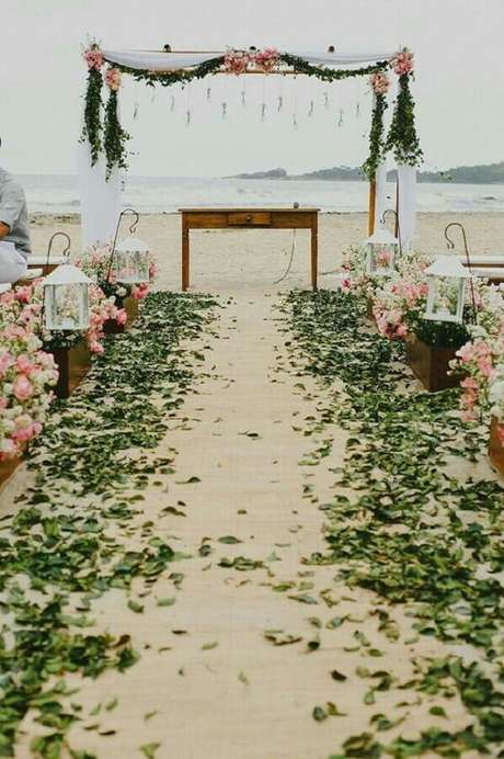 33. Decoração para casamento ao ar livre com arranjo de flores e folhas verdes – Foto: A Noiva de Botas