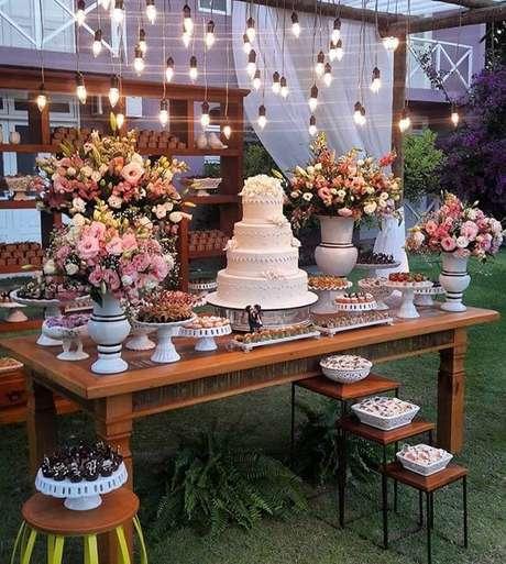 35. Linda mesa de festa de casamento ao ar livre decorada com lumárias pendentes e arranjo de flores – Foto: Doce Sabor – Buffet e Recepção