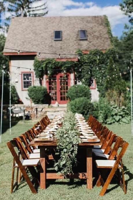 41. Decoração de festa de casamento ao ar livre com varal de luz e arranjo de folhas sobre a mesa dos convidados – Foto: Pinterest