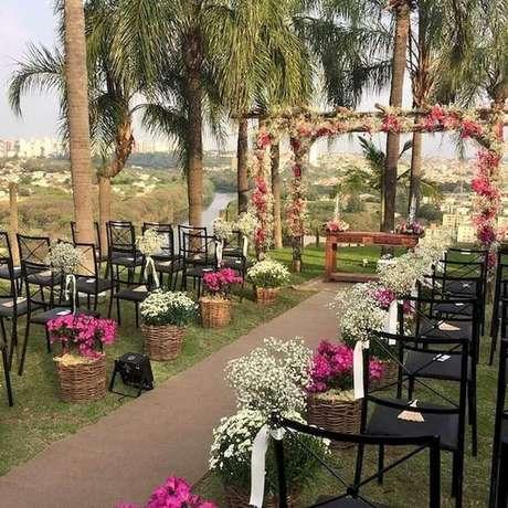 50. Arranjos de flores dentro de cestos rústico são perfeitos para a decoração da cerimônia do casamento simples ao ar livre – Foto: 33Decor