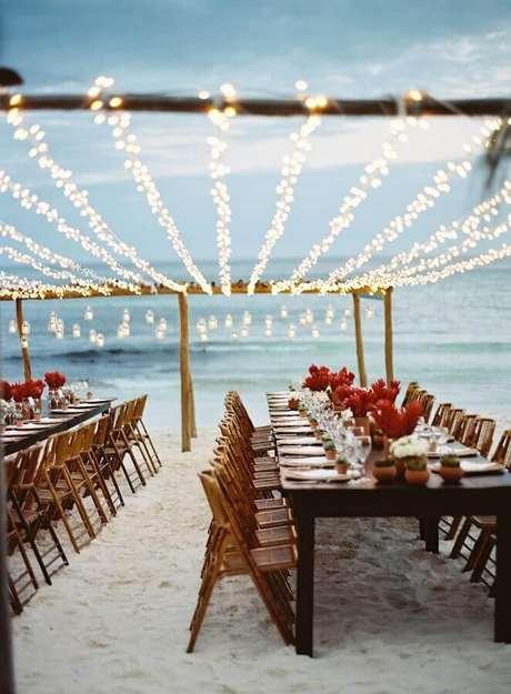 52. Festa de casamento ao ar livre decorada com pisca pisca sobre as mesas – Foto: LM Weddings
