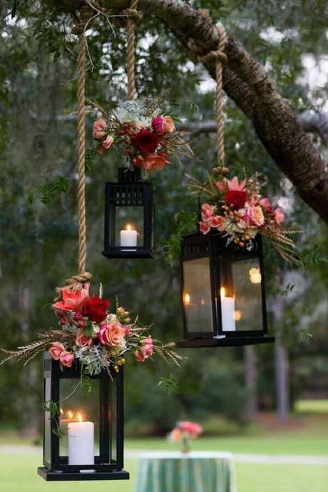 60. As lanternas com velas também pode ser usadas suspensas na decoração de casamento ao ar livre a noite – Foto: The Knot