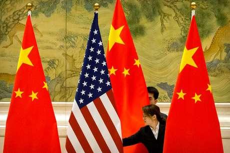 Funcionários ajustam bandeiras da China e dos Estados Unidos antes de rodada de negociações comerciais em Pequim, na China 14/02/2019 Mark Schiefelbein/Pool via REUTERS