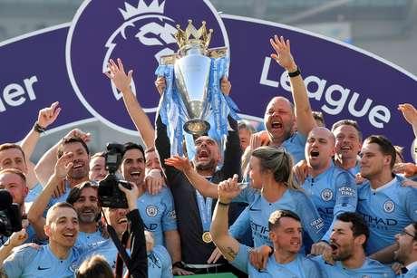 O técnico Pep Guardiola levanta a taça de campeão inglês pelo Manchester City