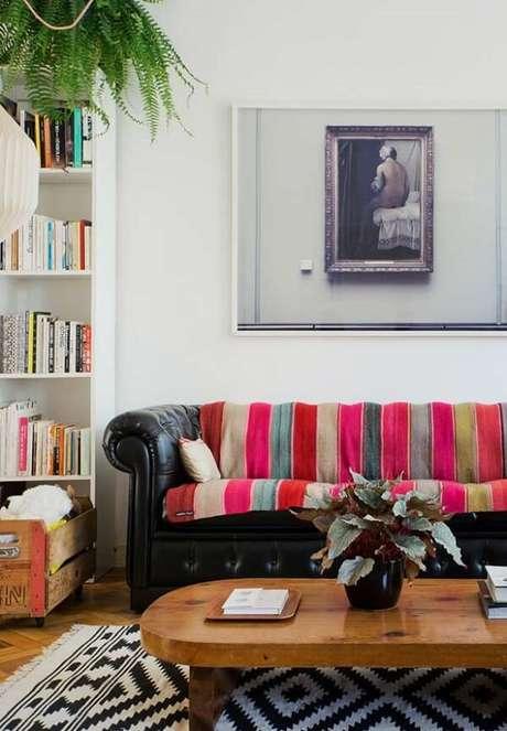 11. A manta listrada colorida sob o sofá preto trouxe alegria para o ambiente. Fonte: Pinterest