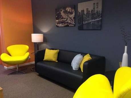 3. Complemente a decoração do escritório com sofá preto e almofada amarela. Projeto de Juliana Lahoz